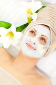 Captivating young woman receiving white cream on her face — Stock Photo