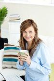 Attractive businesswoman drinking coffee using her laptop sittin — Stock Photo