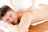 Charismatic relaxed man enjoying a back massage in a spa center — Stock Photo