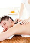 Happy young man enjoying a back massage with hot stone — Stock Photo