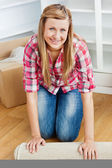 Happy woman roll a carpet out — Stock Photo