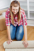 Positive woman roll a carpet out — Stock Photo