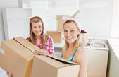 Bright female friends holding boxes — Stock Photo