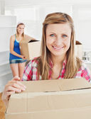 Delighted woman holding boxes after moving — Stock Photo