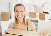 Smiling woman holding boxes after moving — Stock Photo