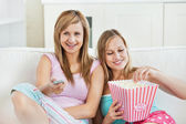 Relaxed female friends eating popcorn watching tv — Stock Photo