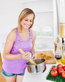 Merry woman cooking spaghetti at home — Stock Photo