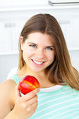 Pretty caucasian woman holding an apple at home — Stock Photo