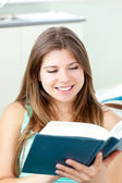 Parlak beyaz kadın evde kitap okurken — Stok fotoğraf