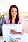 Junge caucasian frau mit einer nähmaschine in der küche — Stockfoto