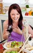 Delighted woman eating her meal holding a glass of wine at home — Stock Photo