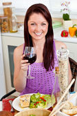 Charming woman eating her meal holding a glass of wine at home — Stock Photo