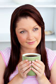 Positive woman holding a cup of coffee at home — Stock Photo