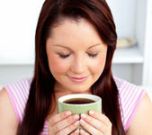 Delighted woman holding a cup of coffee at home — Stock Photo