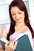 Konsantre kadın evde kitap okurken — Stok fotoğraf
