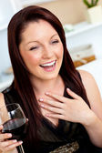 Delighted woman holding a wine of glass at home — Stock Photo