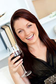 Smiling woman holding a wine of glass at home — Stock Photo