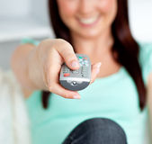 Close-up of a smiling woman hoding a remote in the living-room — Stock Photo