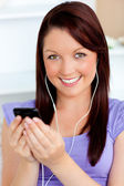 Happy woman using her cellphone to listen to music with earphone — Stock Photo
