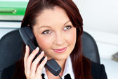 Assertive young businesswoman talking on phone smiling at the ca — Stock Photo
