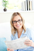 Positive businesswoman reading newspaper in the office — Stockfoto