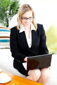 Ambitious businesswoman using her laptop sitting on the sofa — Stock Photo