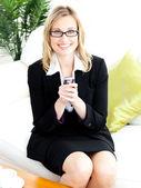 Charmosa empresária enviando um texto sentado no sofá — Fotografia Stock