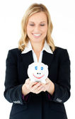Charming businesswoman holding a piggy-bank — Stock Photo
