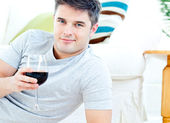Charming caucasian man holding a wineglass in the living-room — Stock Photo