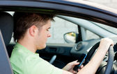 Concentrated man sending a text sitting in his car — Stock Photo