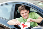"""Happy young man cutting a """"L"""" sign sitting — Stock Photo"""