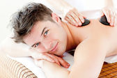 Handsome man receiving a back massage with hot stone — Stok fotoğraf