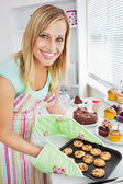 Smiling woman holding cookies in the kitchen — Stock Photo