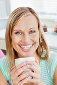 Glowing woman holding a cup of coffee at home — Stock Photo