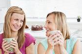 Delighted female friends holding a cup of coffee at home — Stock Photo