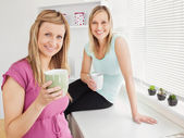 Portrait of two happy women holding cups of coffee at home — Stock Photo