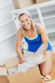 Attractive woman unpacking a box on the floor — Stock Photo