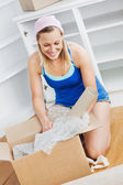 Charming woman unpacking a box on the floor — Stock Photo