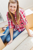 Smiling woman unpacking a box on the floor — Stock Photo