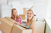 Two radiant women carrying boxes at home — Stock Photo