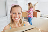 Two positive women carrying boxes at home — Stock Photo