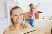 Two joyful women carrying boxes at home — Stock Photo