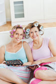Smiling female friends with hair rollers eating chocolate readin — Stock Photo