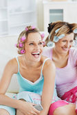 Female friends with hair rollers watching televison on the sofa — Stock Photo