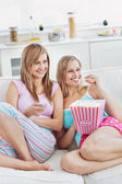 Two smiling female friends watching televison on the sofa eating — Stock Photo