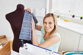 Merry woman sewing clothes at home — Stock Photo