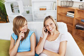 Two happy women using a cellphone at home — Stock Photo