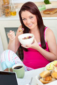 Attractive caucasian woman having breakfast smiling at the camer — Stock Photo