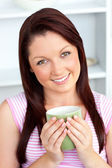 Cheerful woman holding a cup of coffee in the kitchen — Stock Photo