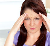 Dejected woman having a headache sitting in the living-room — Stock Photo